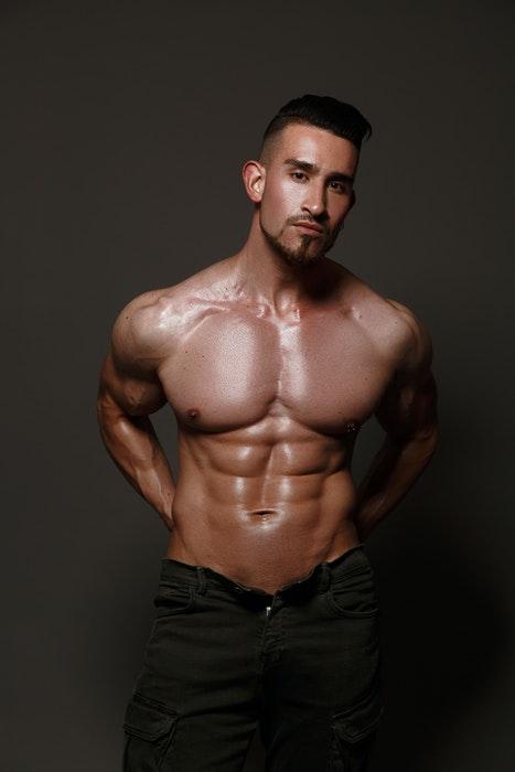 Foto de banheiro de um modelo masculino seminu em pé na frente de um fundo neutro
