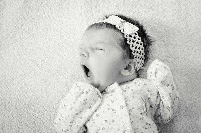 Black and white photo of a newborn baby in a cute romper outfit