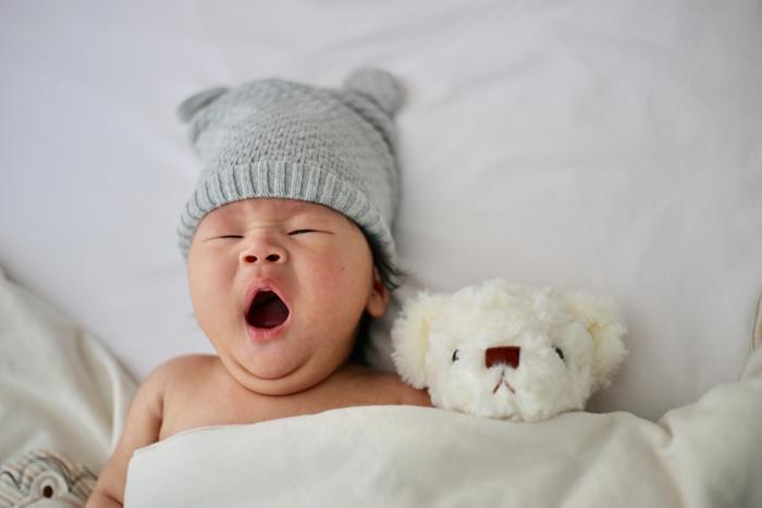 foto de um bebê recém-nascido em uma roupa fofa posou com um ursinho de pelúcia