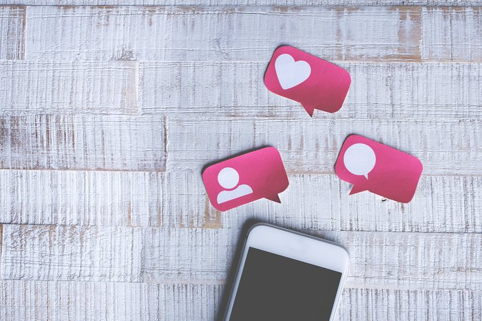 A smartphone with paper speech bubbles above it with social media icons on them