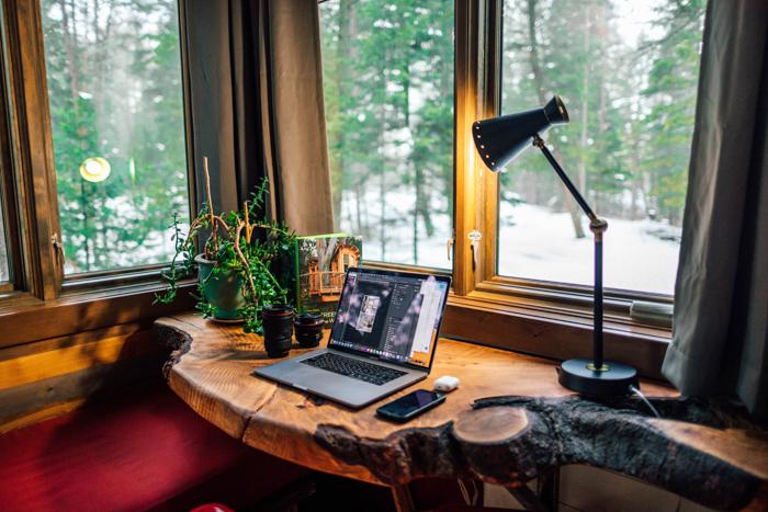 foto de um laptop em uma mesa de madeira perto da janela