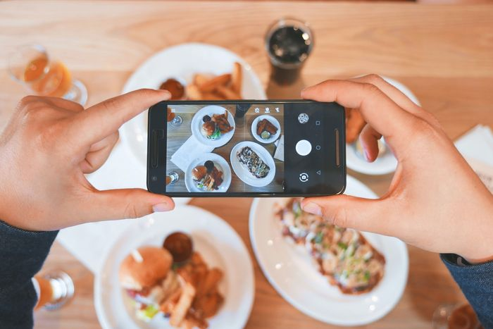 photo of hands holding a smartphone to take a photo of plates of food
