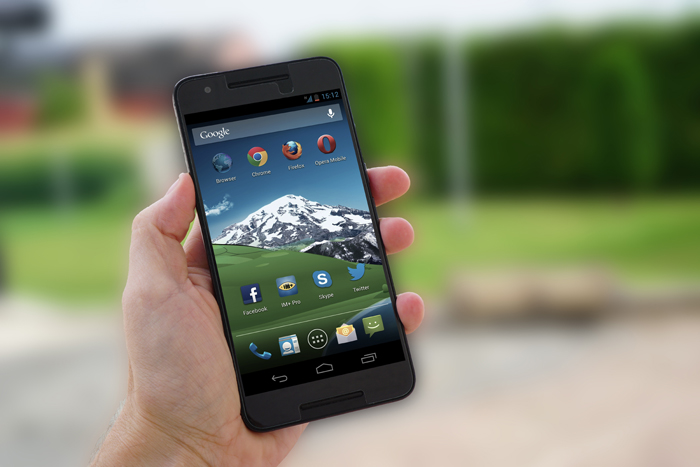 A hand holding a smartphone outdoors