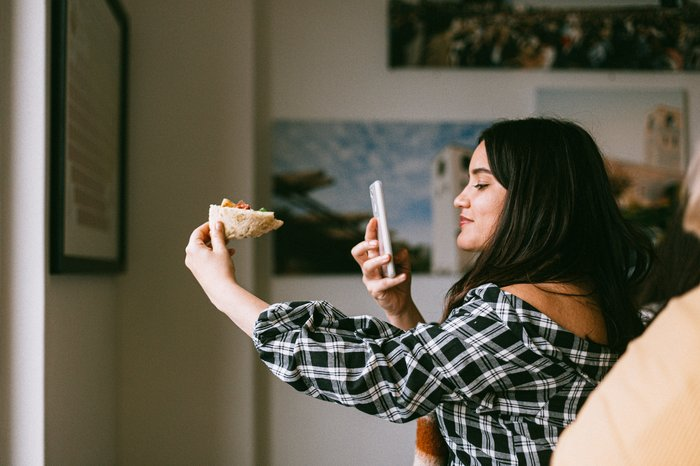 A girl taking a food photo with her smartphone