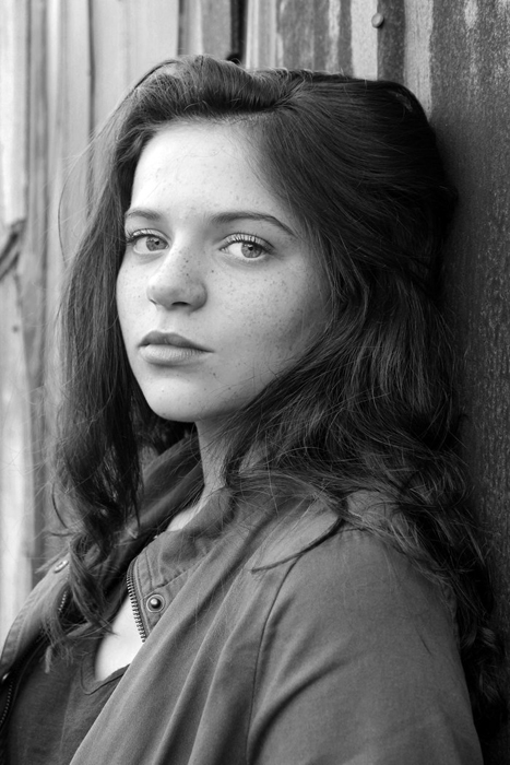 Black and white portrait of a girl against a wall