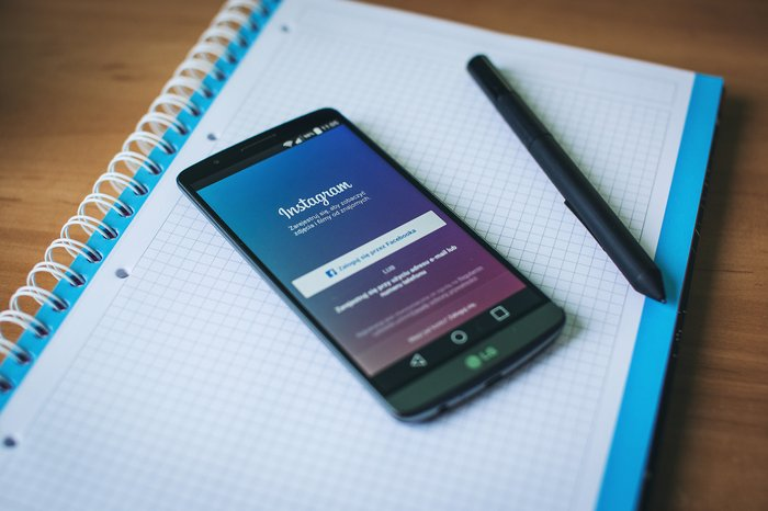 A smartphone opened on Instagram, on top of a notebook