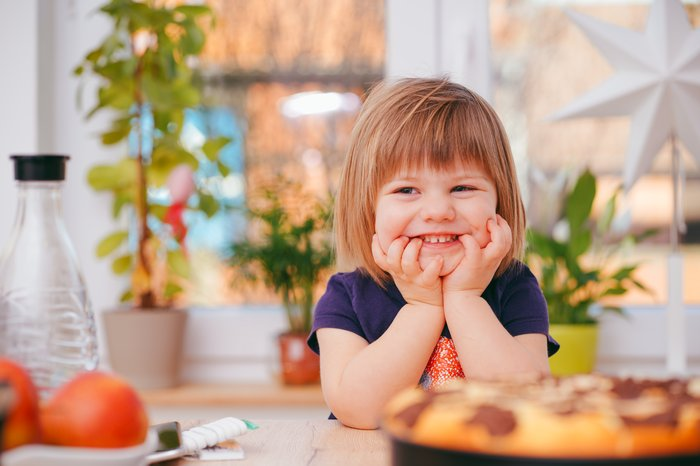 Cute lifestyle portrait of a little girl at a kitchen table