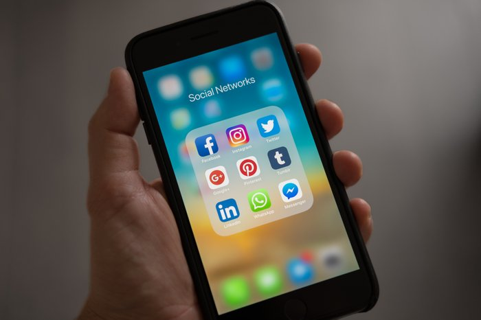 A hand holding a smartphone with social media apps onscreen