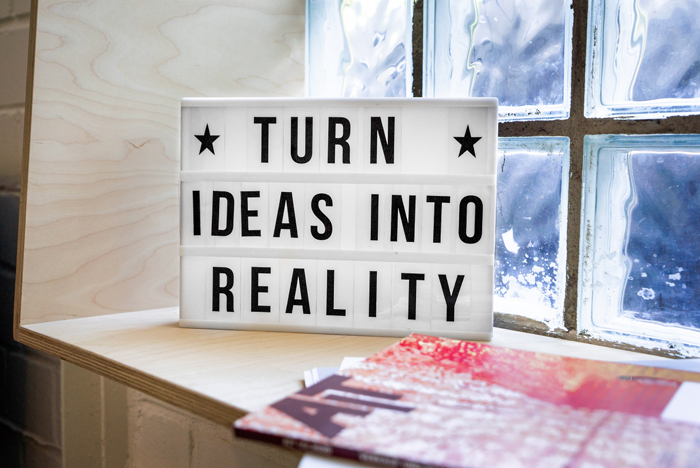 A cute sign saying 'turn ideas into reality' on a windowsill
