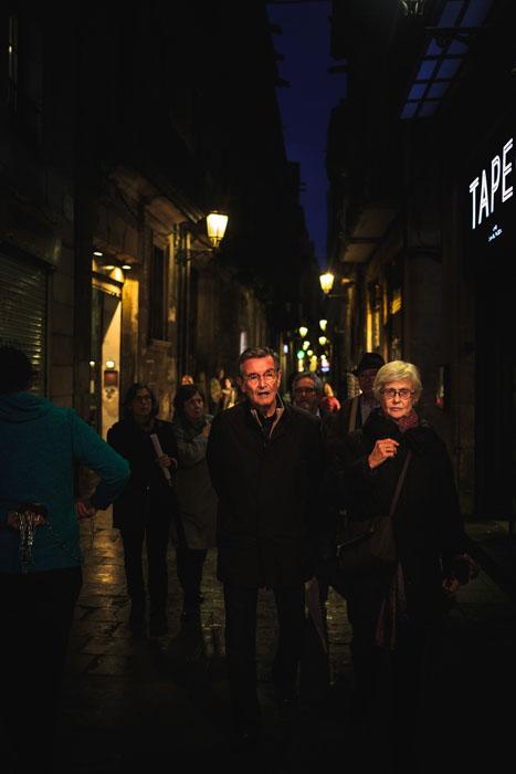 Pessoas andando por ruas movimentadas à noite.