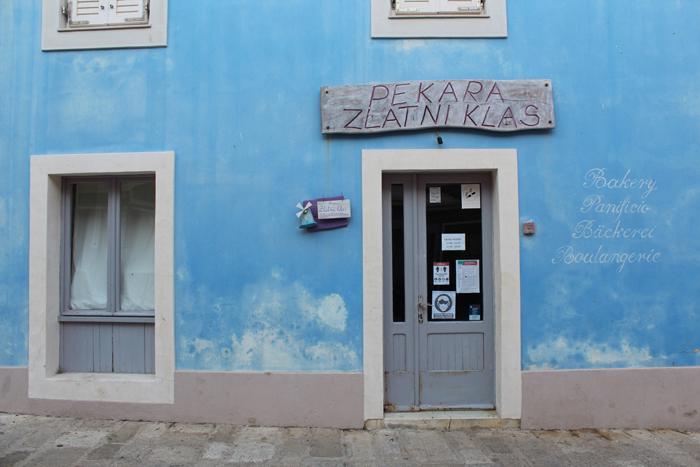 uma foto de uma porta dentro de um prédio azul tirada com uma Canon 1300D