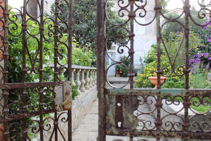 uma imagem de um jardim através de um portão de ferro tirada com uma Canon 1300D