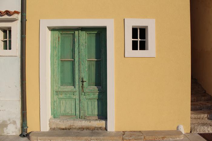 uma imagem de uma porta verde dentro de um prédio amarelo com uma pequena janela à sua direita