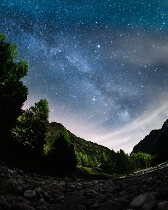 Fisheye astrophotography shot of a star filled sky over a landscape