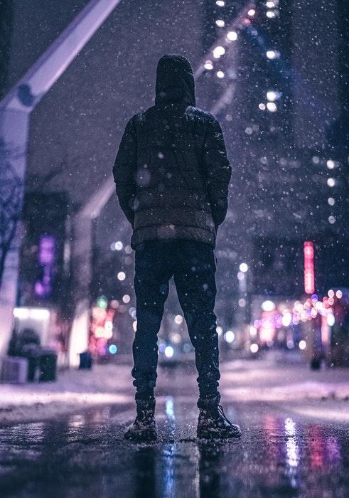 Um homem com roupas de inverno parado em uma rua da cidade enquanto está nevando