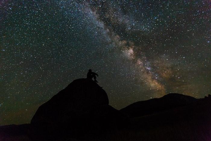 Foto de astrofotografia impressionante da silhueta de um homem em uma rocha em frente a um céu estrelado