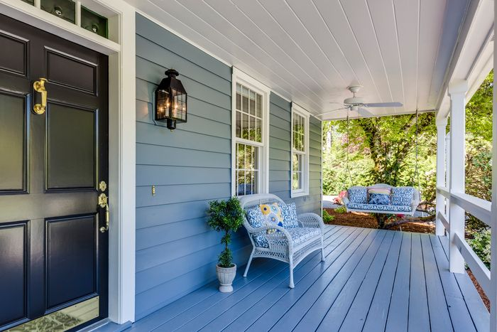 photo of a lovely porch with a blue sofa and a swing
