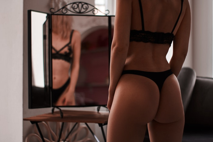A girl in black lingerie posing in front of a mirror