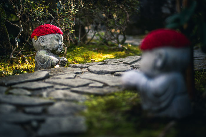 Two stone Buddha sculptures with red knitted hats