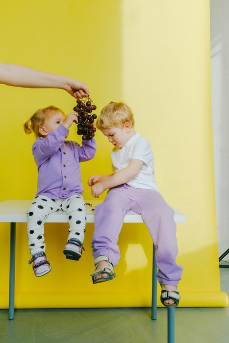 Two kids sitting on a kitchen table eating grapes