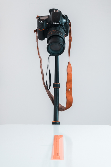 A DSLR camera on a tripod pointing down to a table