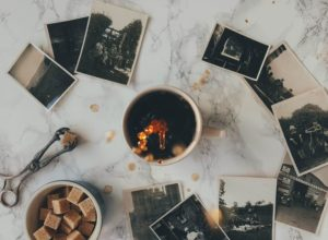 overhead photo of a coffee mug on a table with black and white polaroid photos