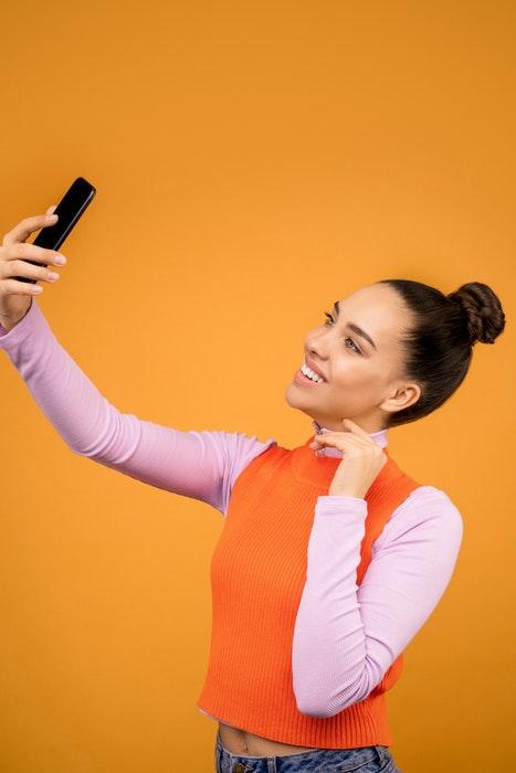 Una mujer joven posando para un selfie de alto ángulo delante de un fondo naranja