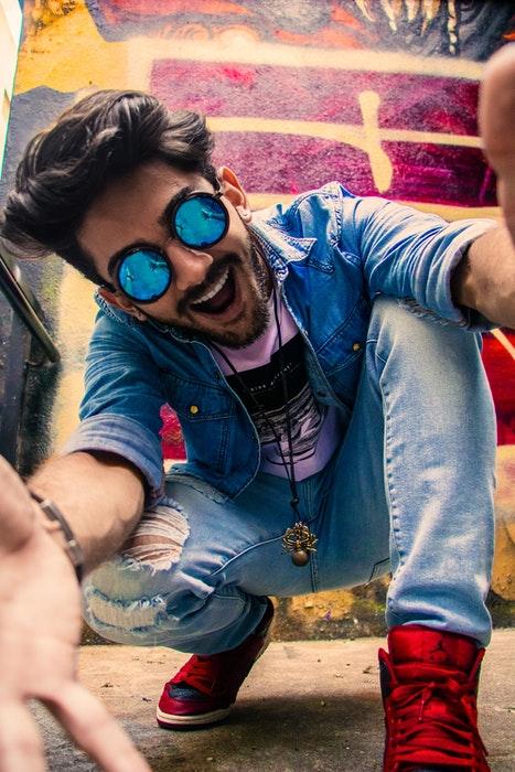 Un joven posando para un selfie frente a graffiti de colores