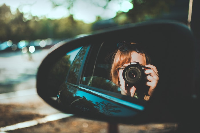 A girl taking a selfie with a DSLR from a car side mirror