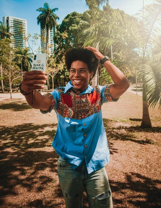 Poses para selfies: Un joven posando para un selfie al aire libre frente a árboles tropicales