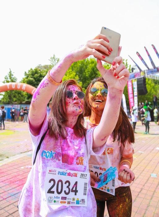 Poses para selfies: Chicas cubiertas de polvo de colores posando para un selfie al aire libre
