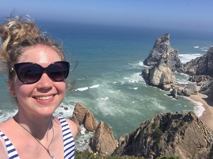 A girl in sunglasses poses for a selfie in front of a beautiful coastal landscape