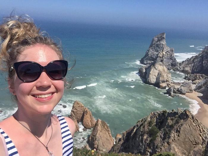 Una chica con gafas de sol posa para una selfie frente a un hermoso paisaje costero