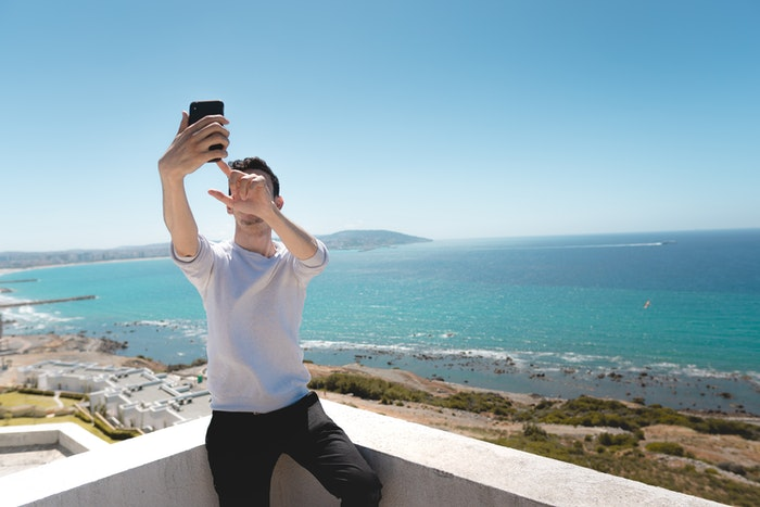 A young man taking a selfie in front of the sea