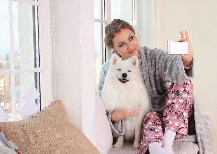 Una chica guapa posando para una selfie con un lindo perro esponjoso