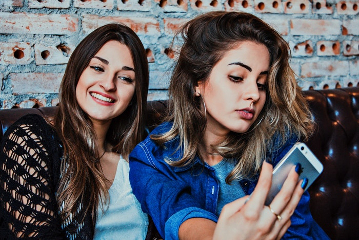 Two teen girls sitting on a couch taking a selfie photo