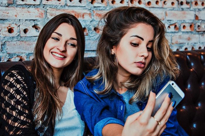 Poses para selfies: Dos chicas adolescentes sentados en un sofá tomando una foto selfie