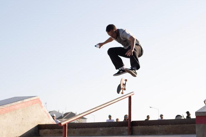 Foto de um patinador em um parque fazendo uma manobra de salto