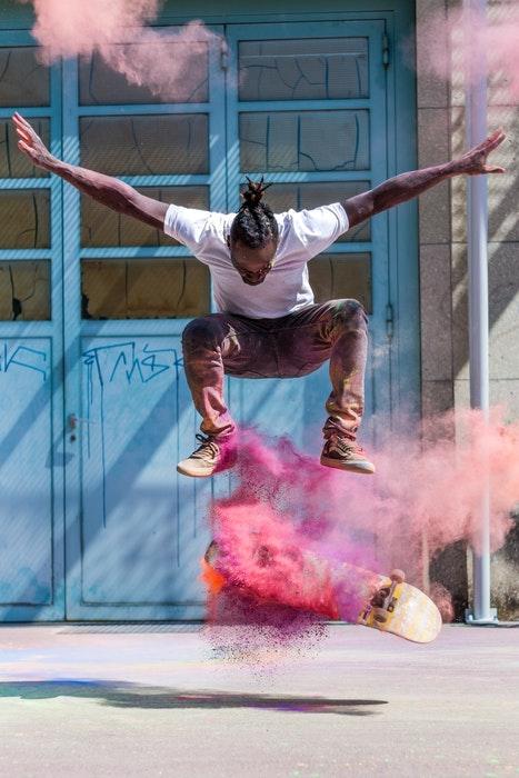 foto de um skate fazendo um truque com pó colorido