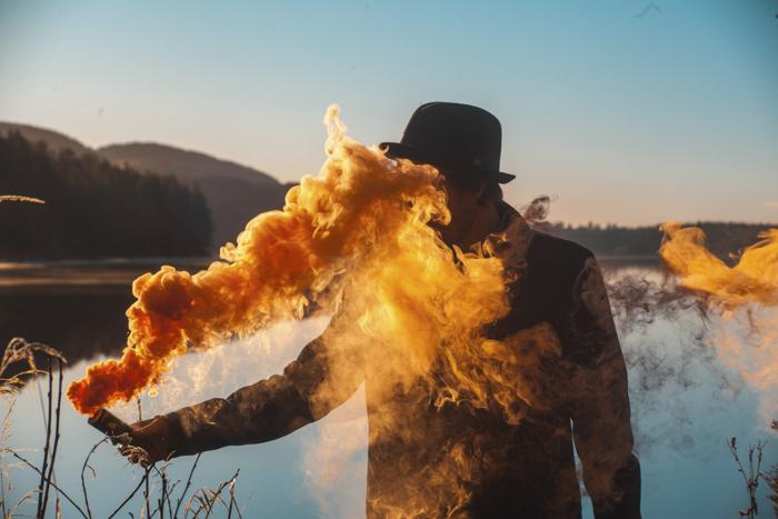 Un hombre que sostiene una granada de humo que emite humo amarillo brillante frente a un paisaje
