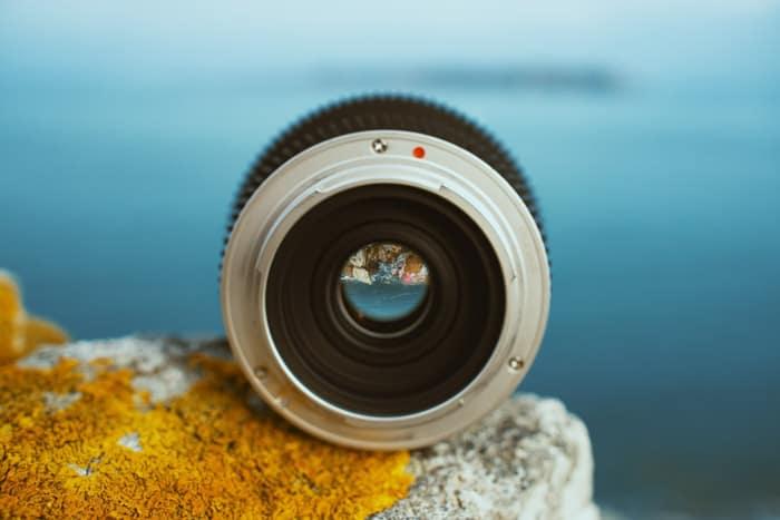 Uma lente de câmera em uma parede de frente para o oceano