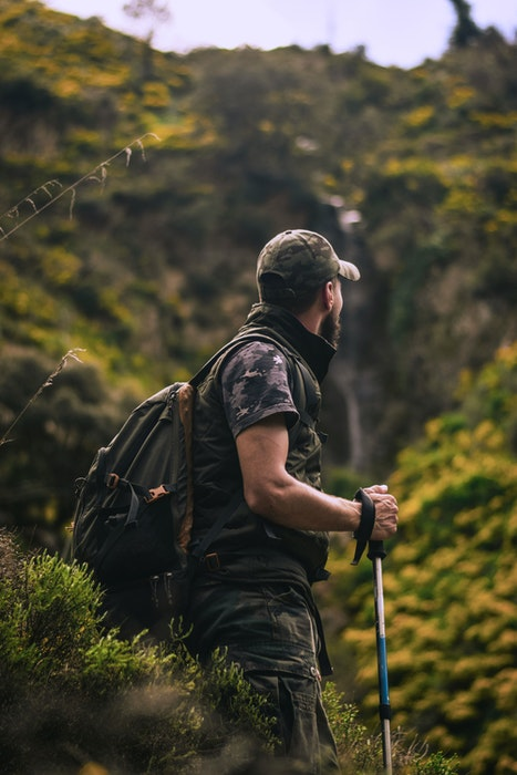 A camouflaged nature photographer on a hike in the wilderness