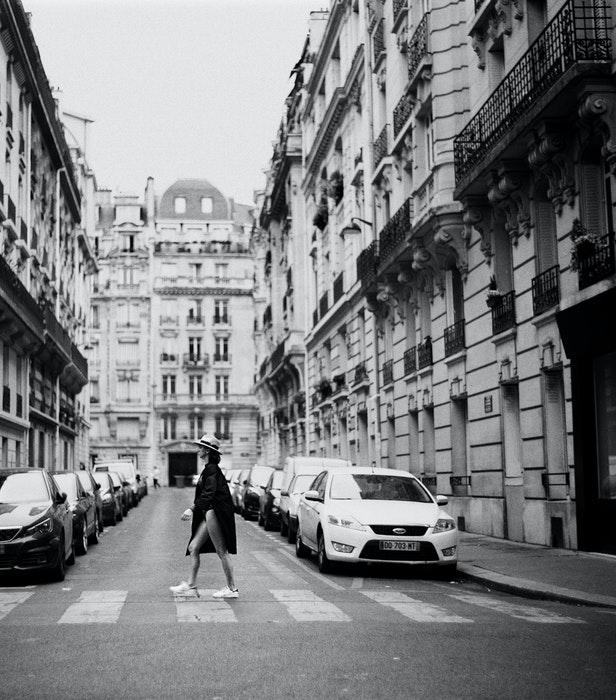Foto em preto e branco de uma garota atravessando a rua