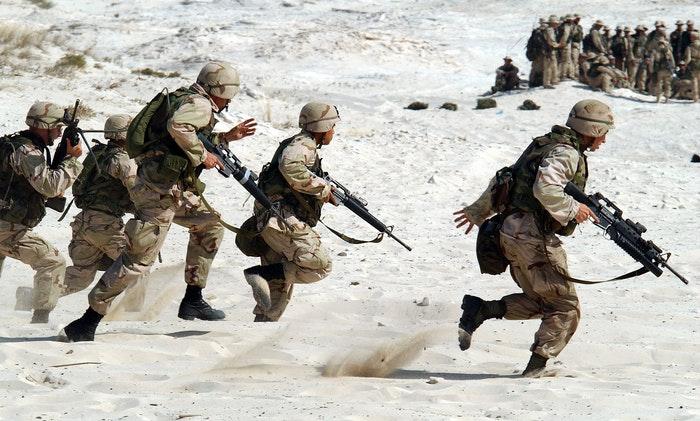 Uma foto de tropas militares correndo na areia.