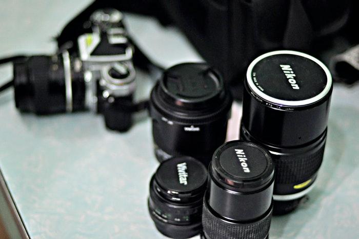 Quatro lentes canon ao lado de uma câmera