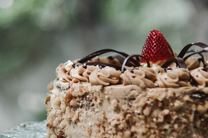 A delicious cake with a strawberry on top creating a focal point