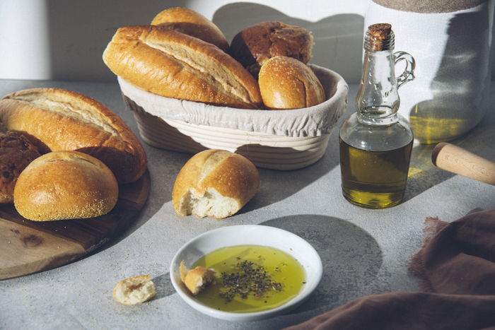 A beautiful food still life of rustic baskets of bread and olive oil