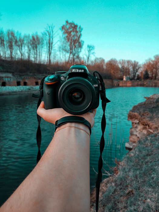A person holding a camera against a beautiful river