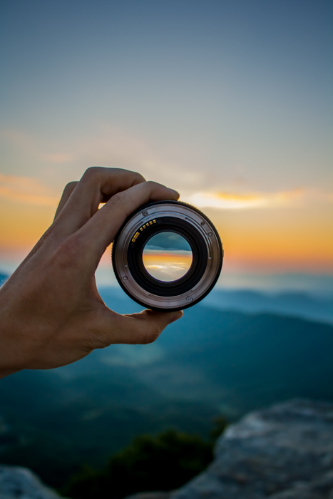 A person holding a camera lens against a stunning sunset