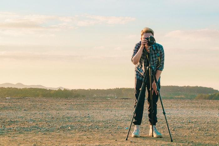 Um fotógrafo montando uma foto DSLR em um tripé